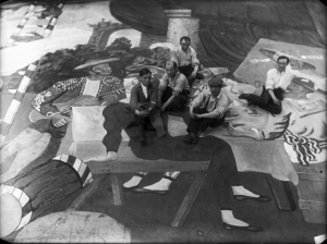 Pablo Picasso (in the beret) and scene painters working on set design for Leonid Massine's Parade, staged by Serge Diaghilev's Ballets Russes in Paris, 1917.